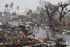 Residents walk on a road littered with debris after Super Typhoon Haiyan battered Tacloban city in central Philippines